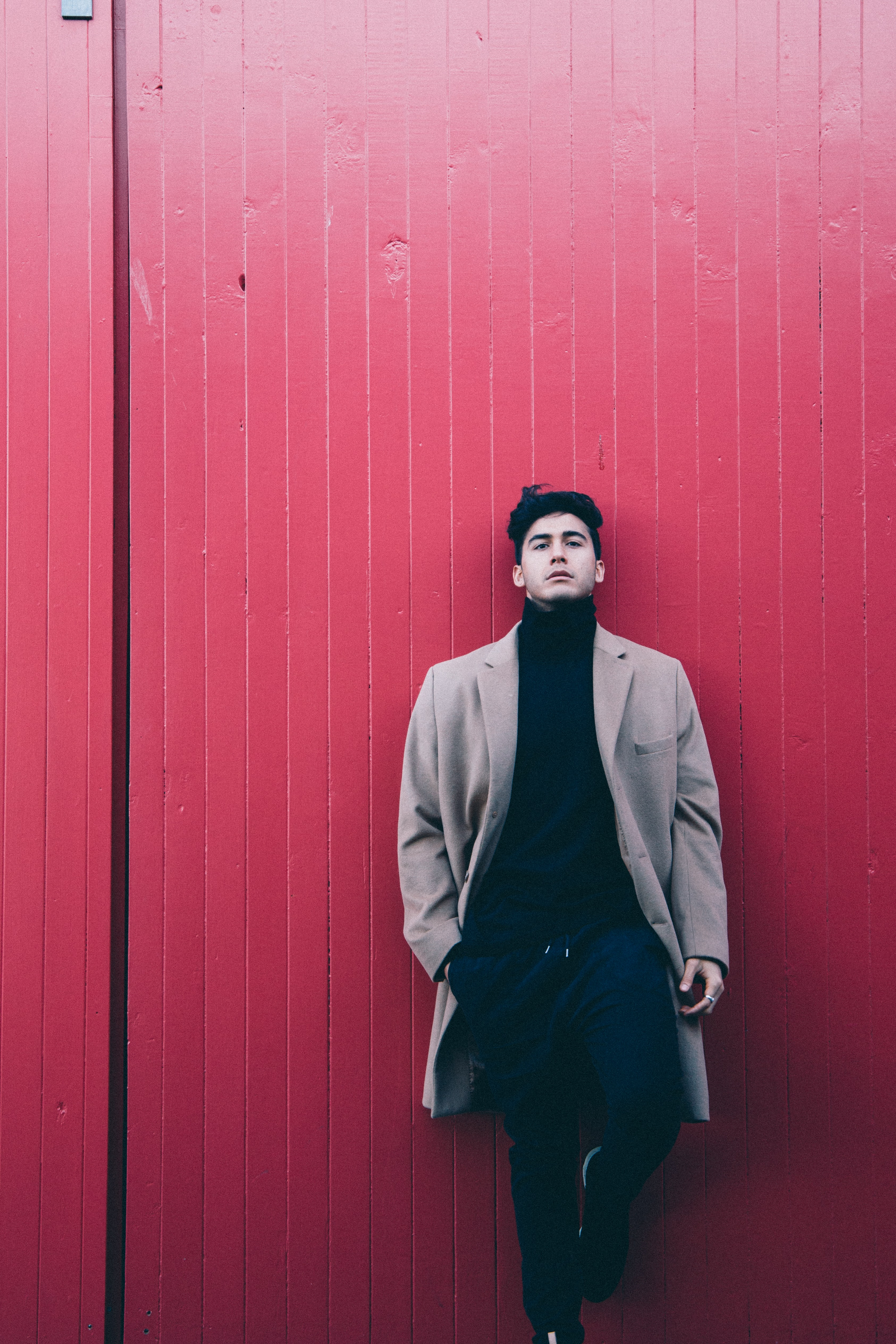man wearing coat leaning on red wall