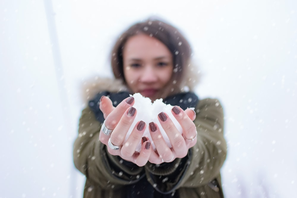 woman holding snow at daytime