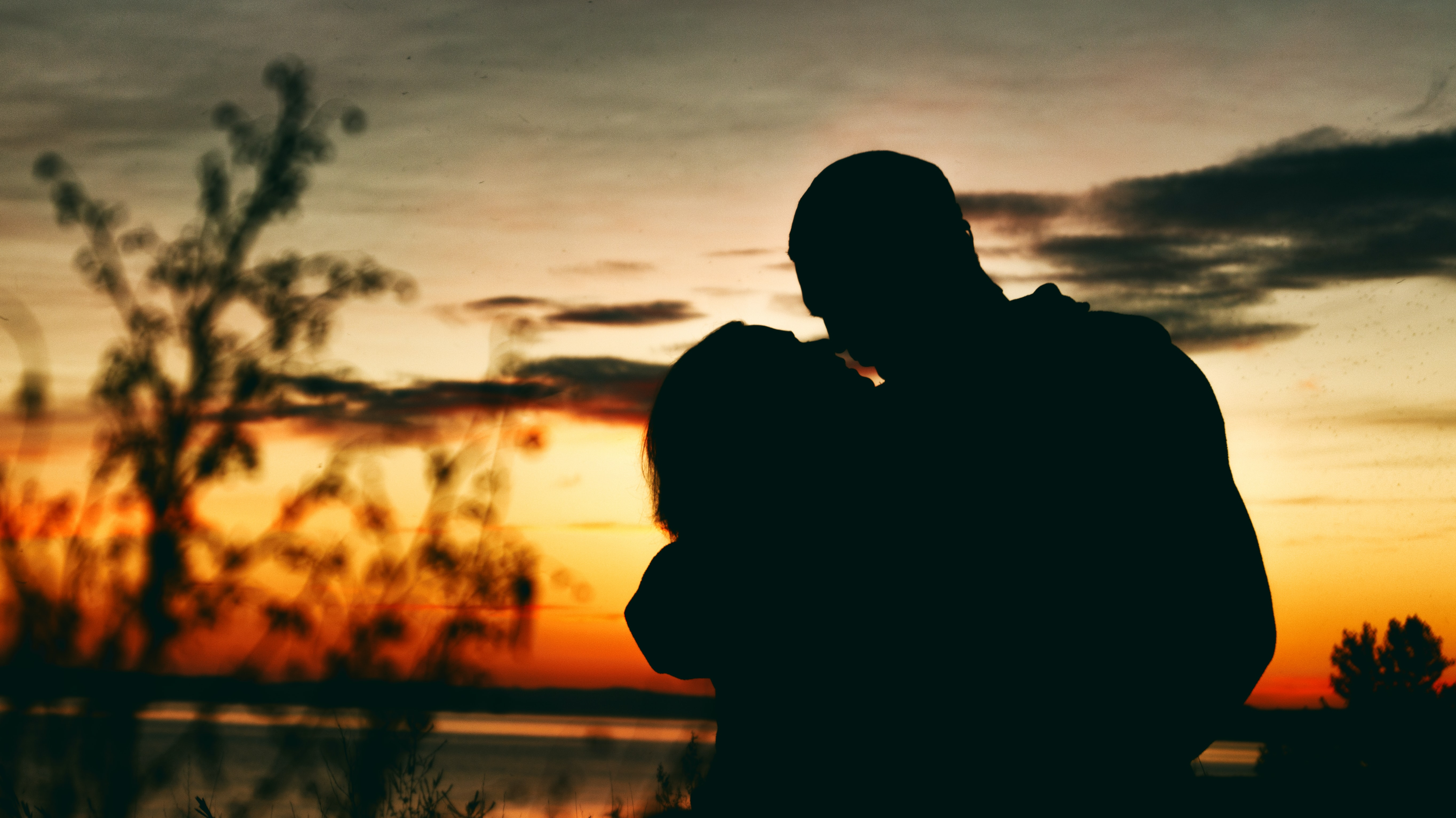 silhouette of man and woman hugging during sunset