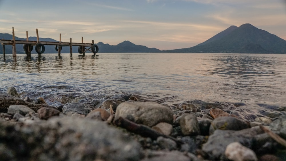brown wooden dock over body of water and mountain during daytime