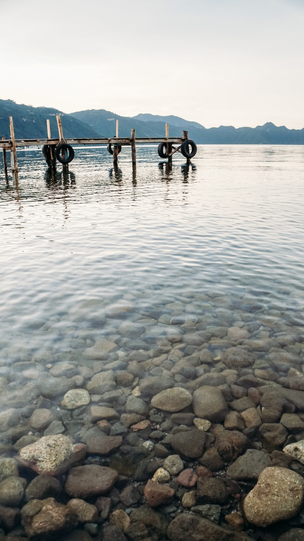 dock on water with stone at daytime