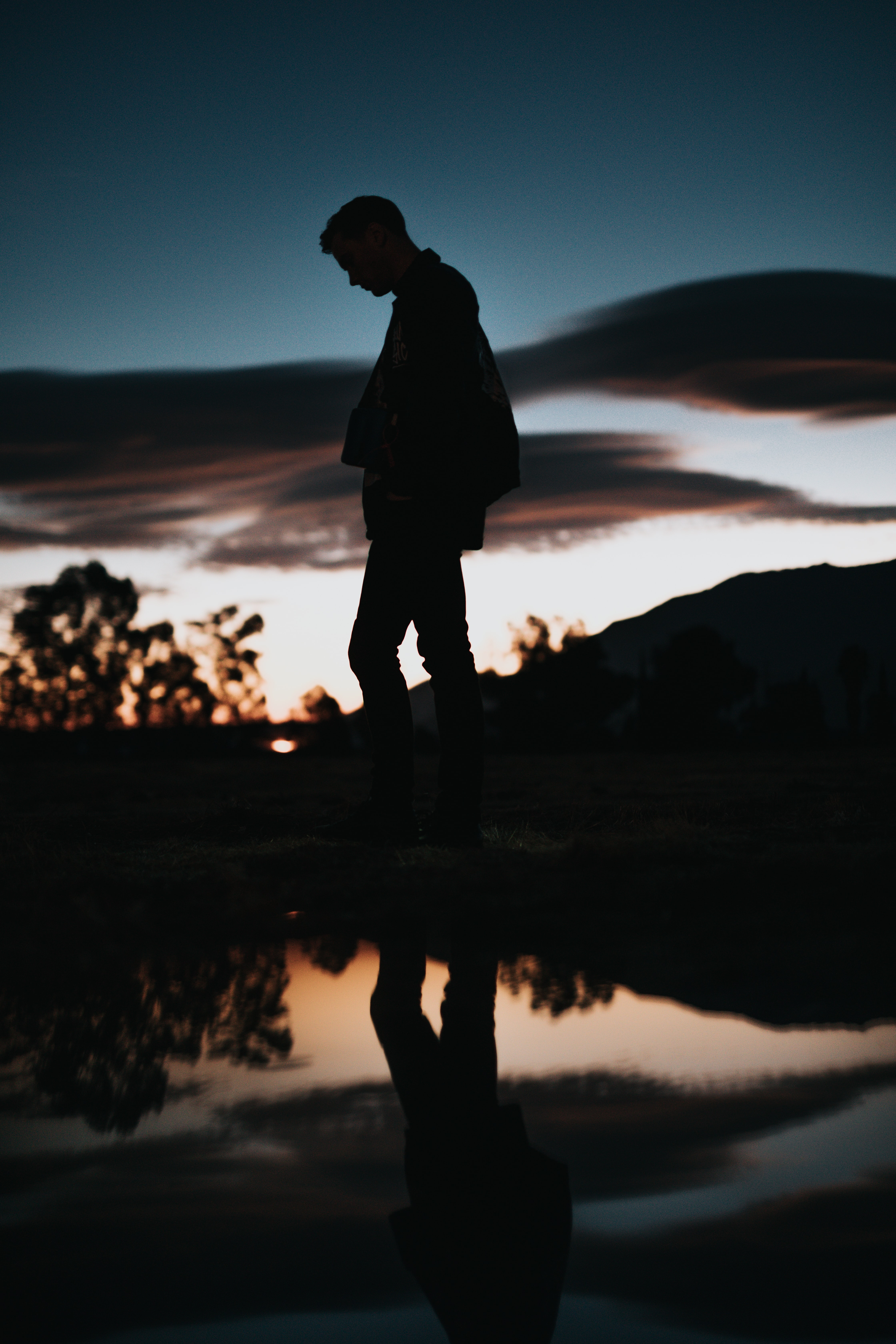 silhouette of man near body of water