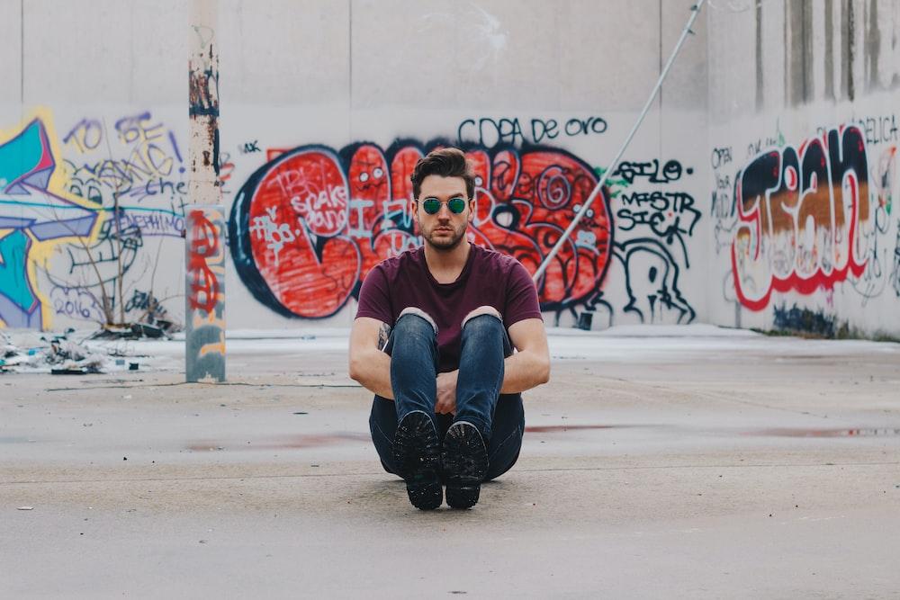 man wearing purple shirt sitting in front of graffiti wall