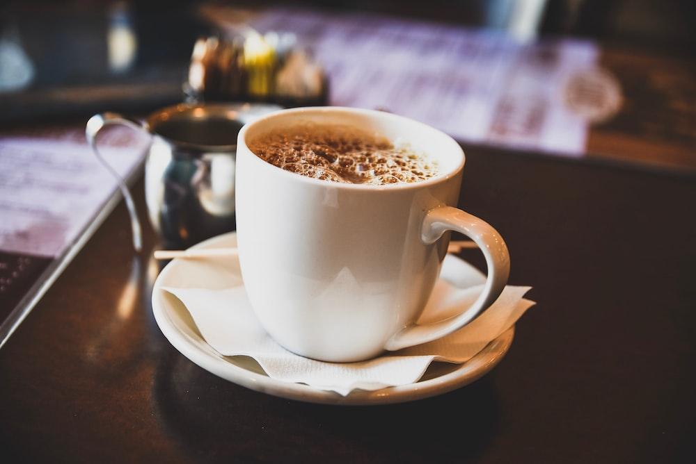 beverage filled mug on saucer on table