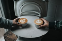 two person holding cappuccino coffee cups