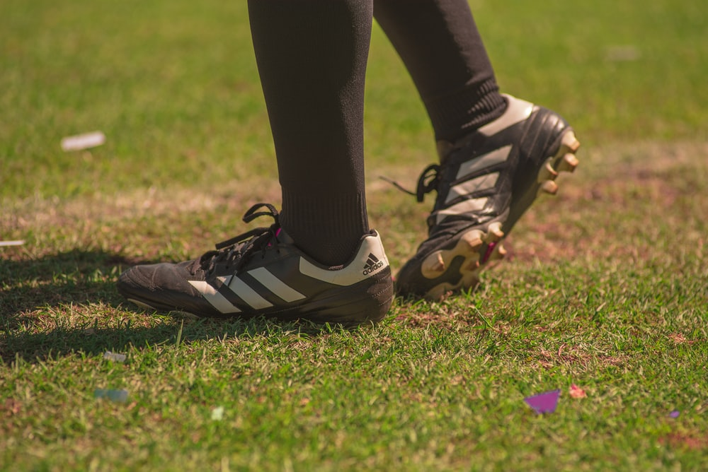 person wearing black-and-white adidas cleats standing on field