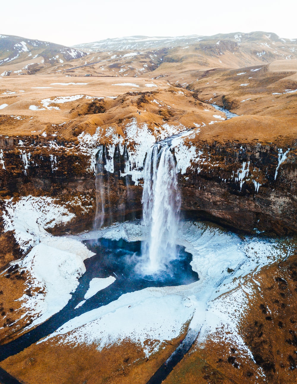 aerial photography of waterfalls near mountains at daytime