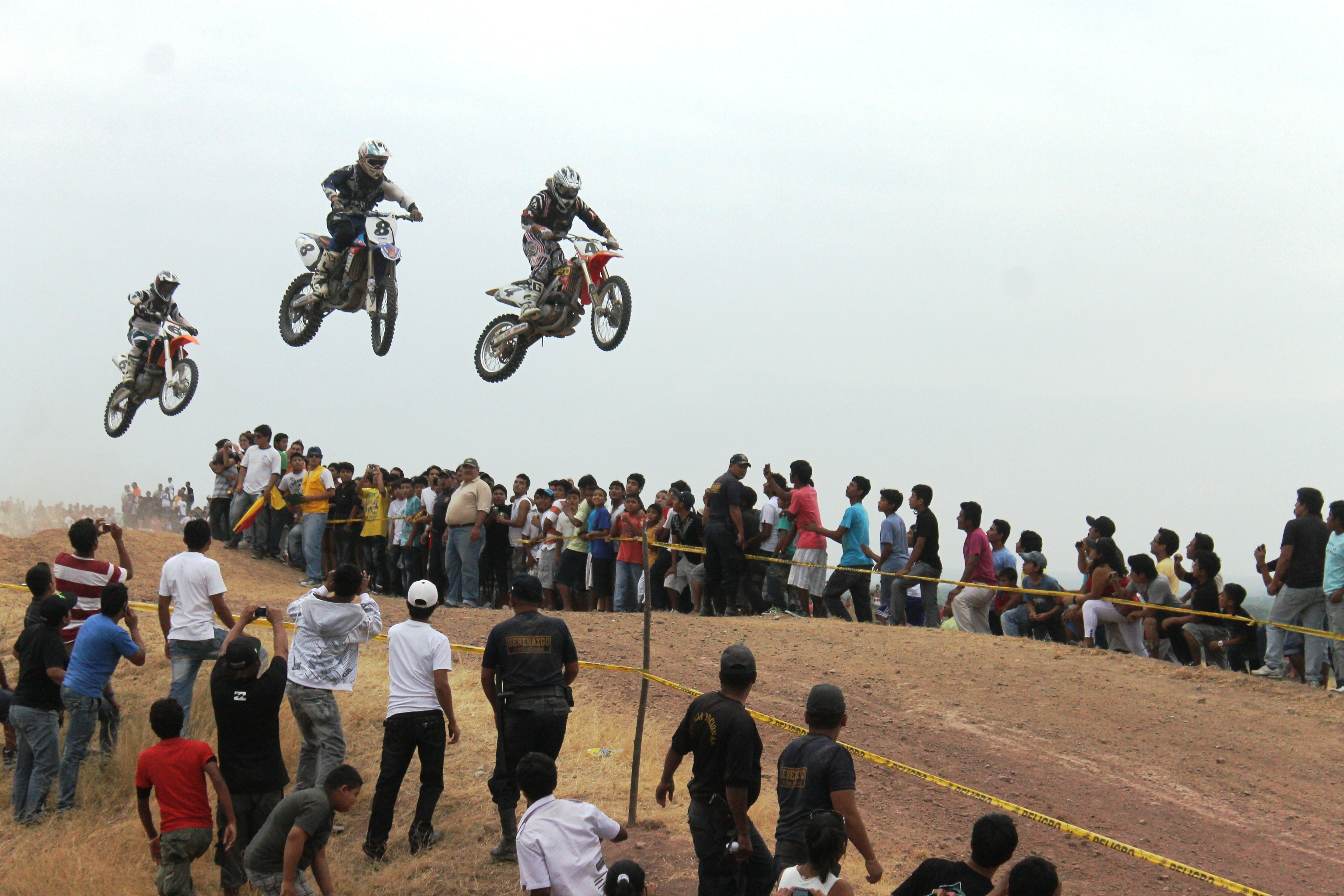 three men riding motocross dirt bikes in mid air near people during day