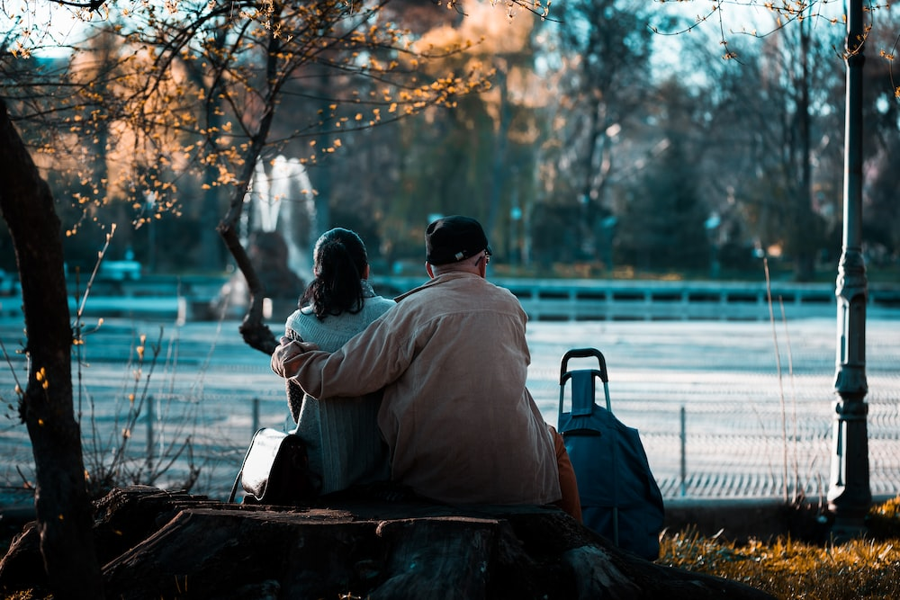 man and woman sitting on pack