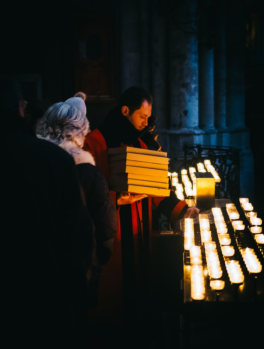 man in red coat holding white boxes holding candle