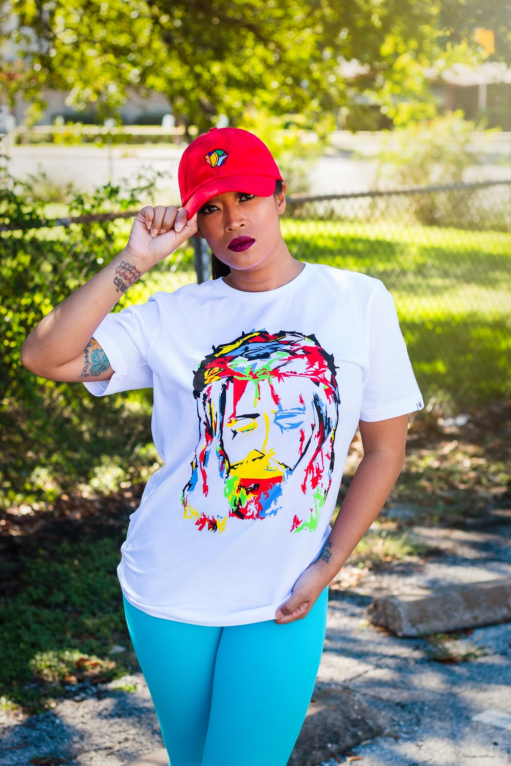 woman wearing cap, t-shirt, and teal pants during day