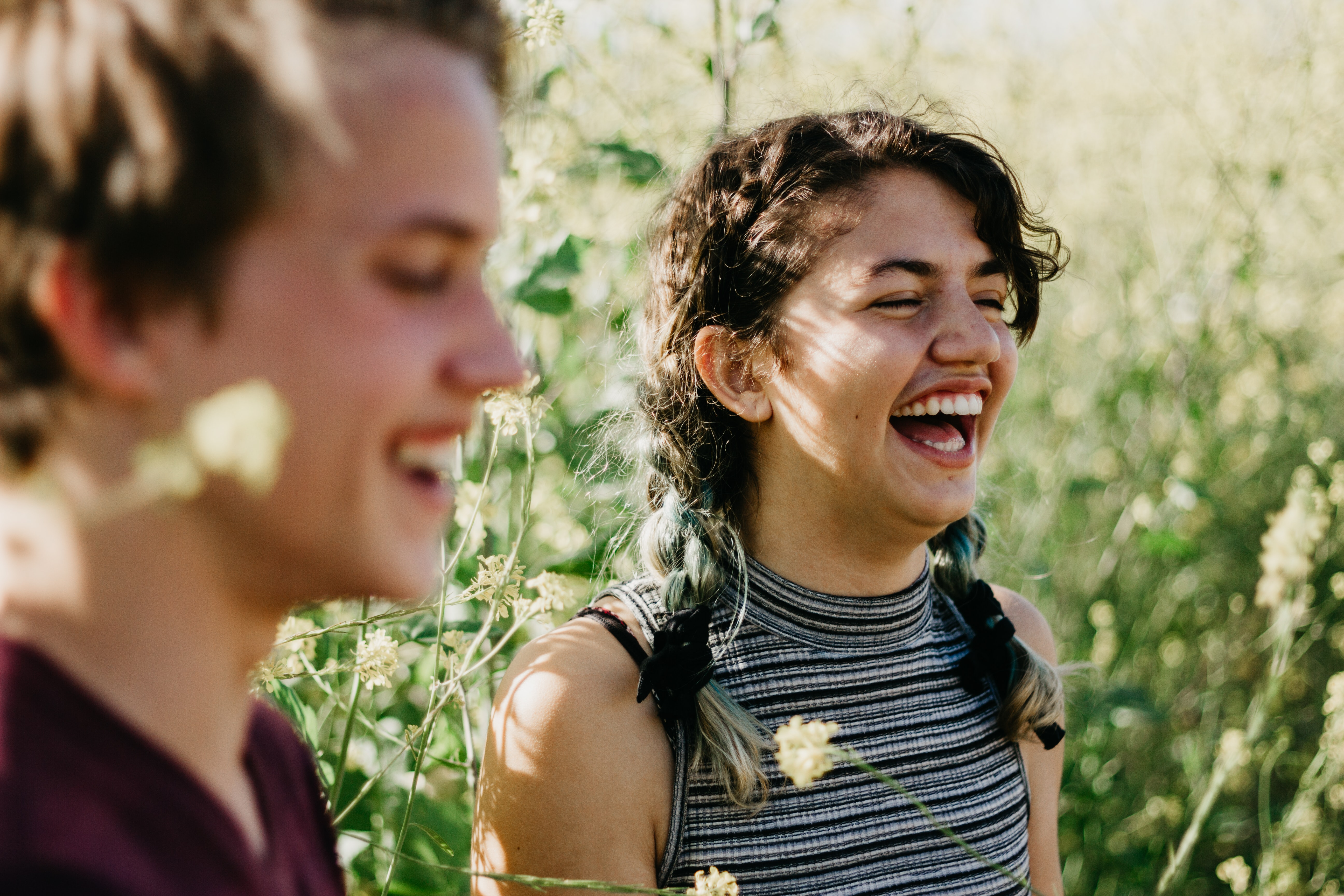 man and woman laughing surrounded with green grass during daytime