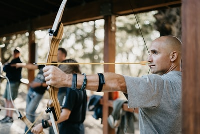 man using a brown bow archery teams background