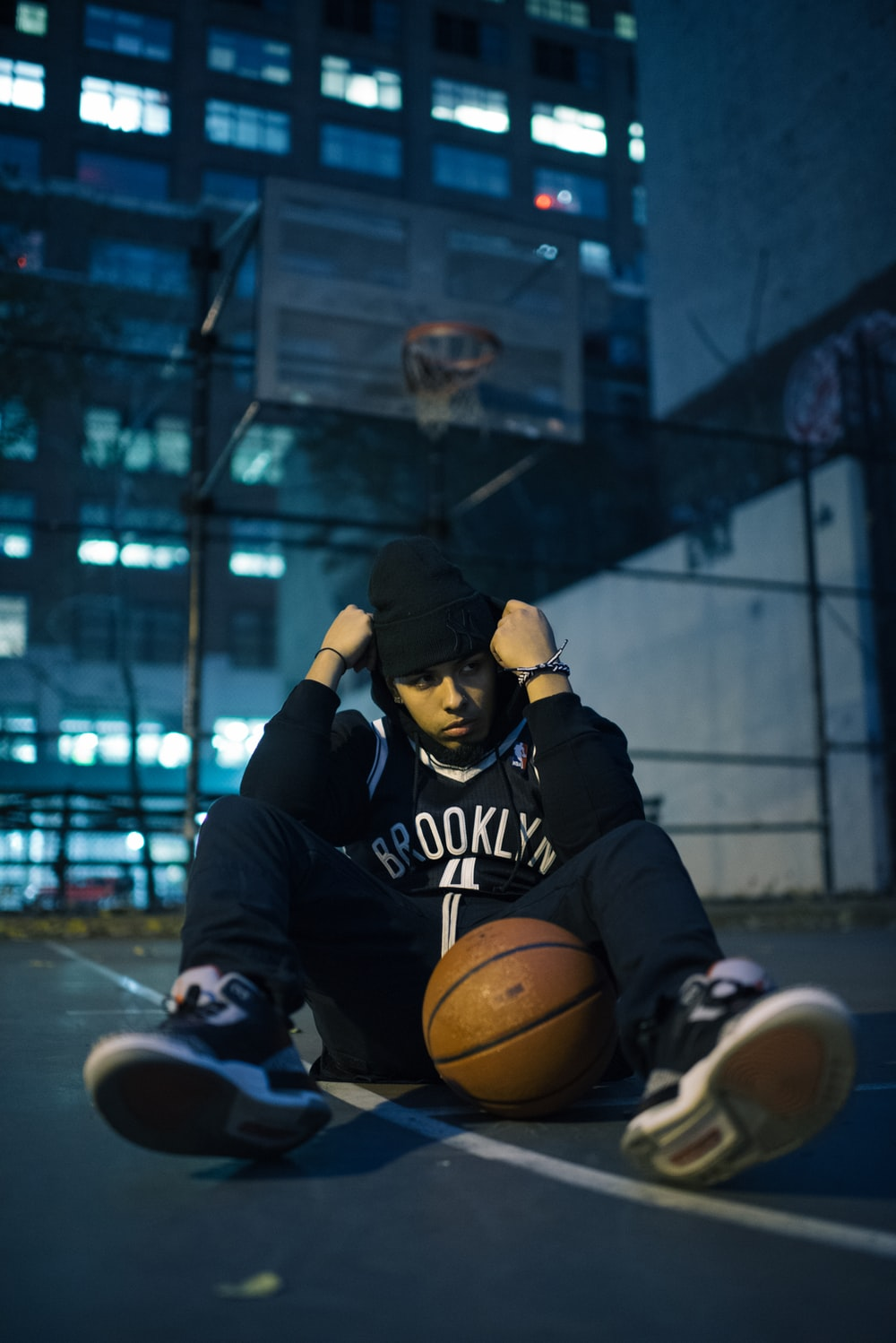 man sitting on basketball court