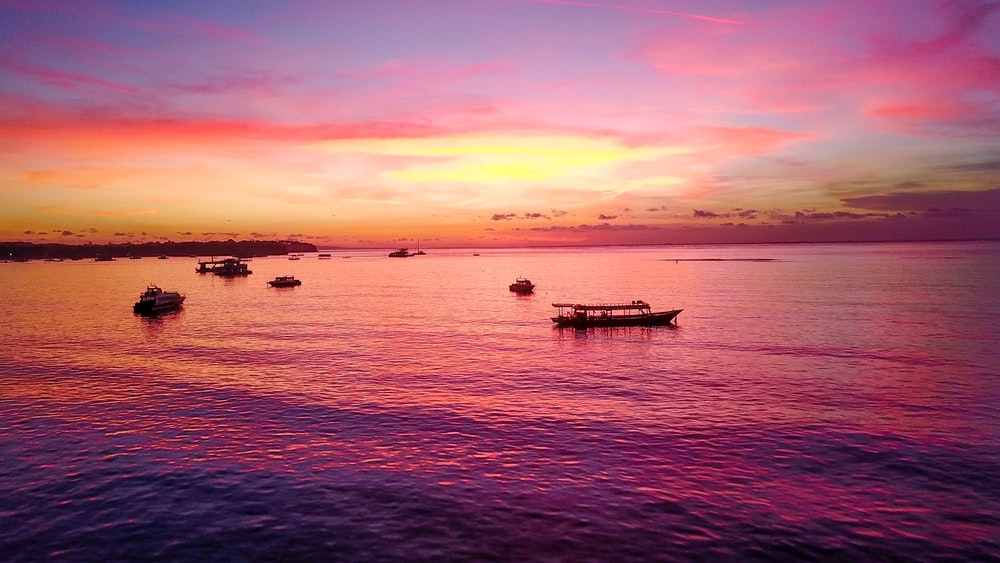 boats on body of water during sunset