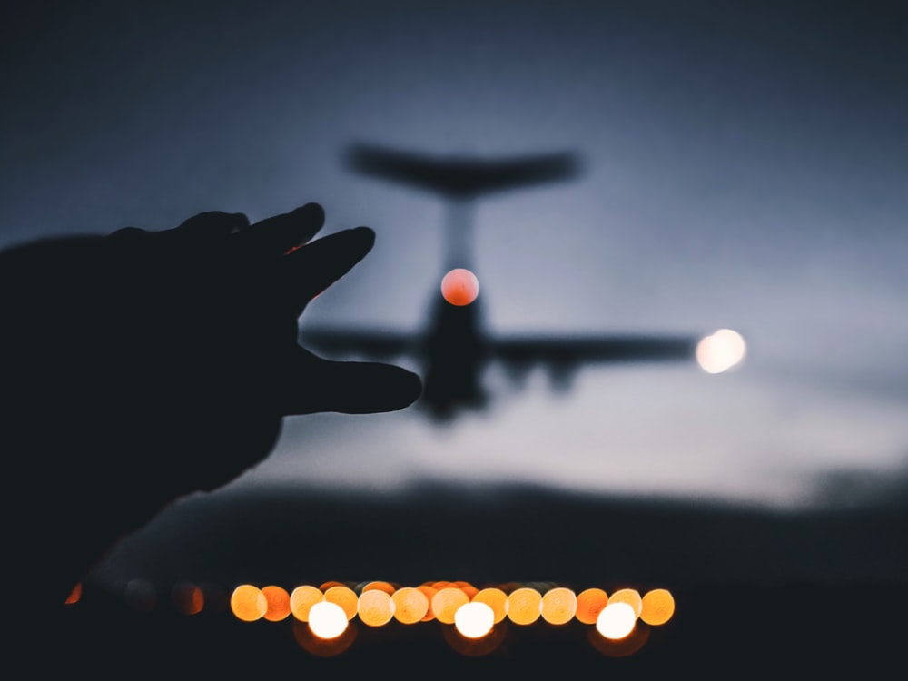 silhouette photo of airplane landing on airline