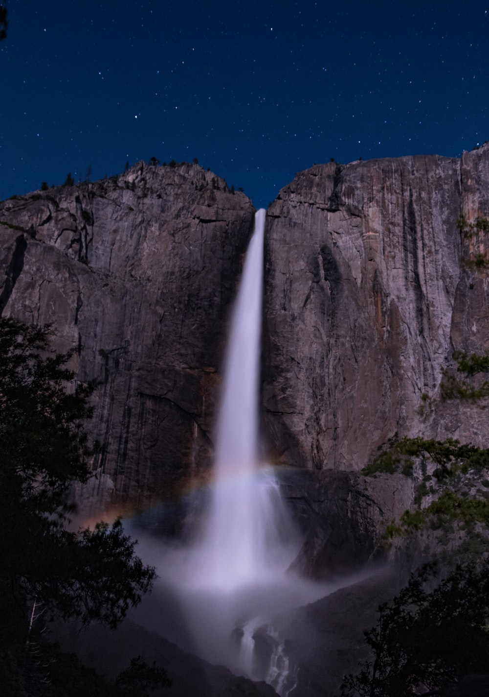 rainbow in front of waterfalls at night time