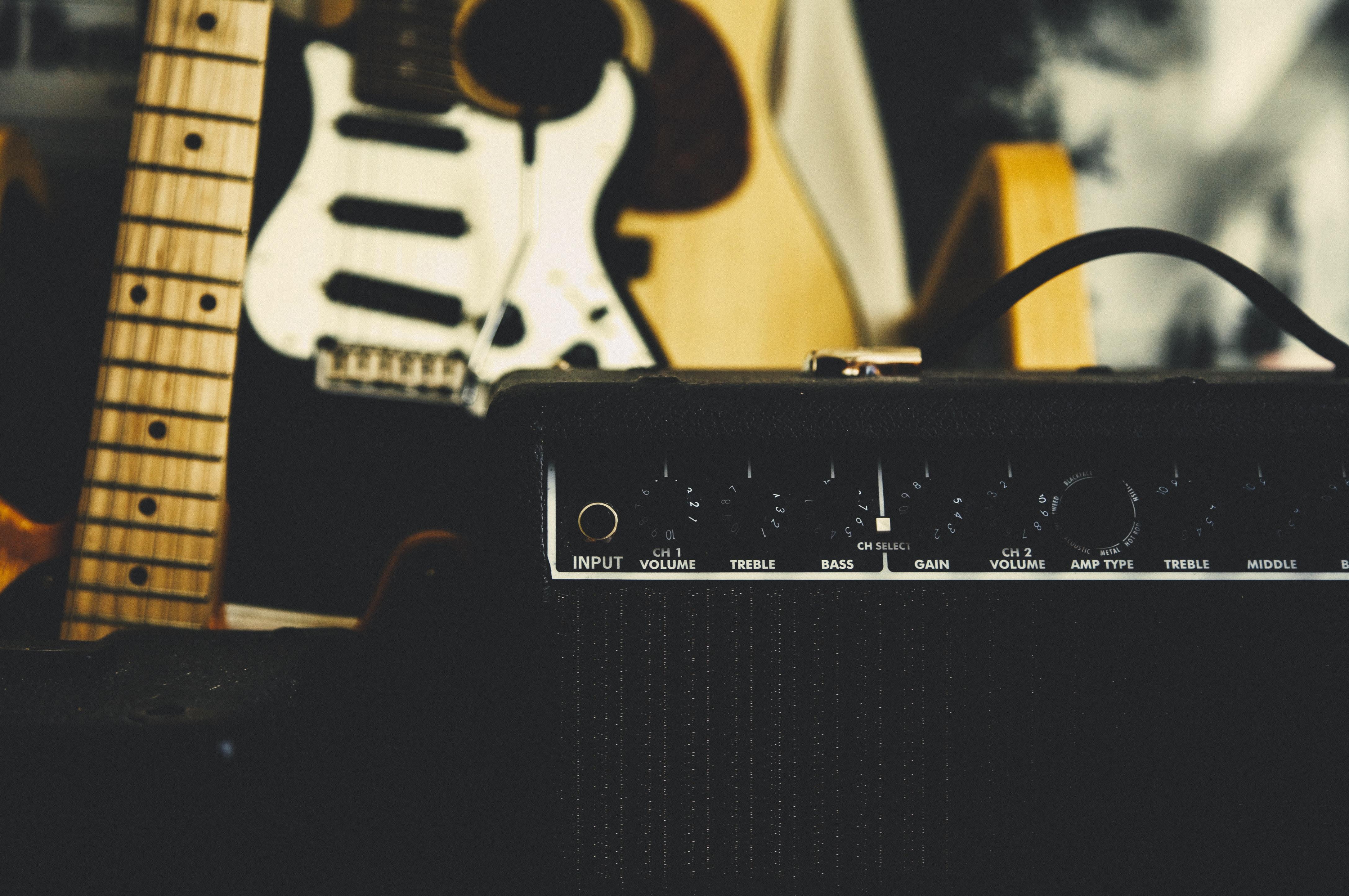black guitar amplifier beside electric guitar