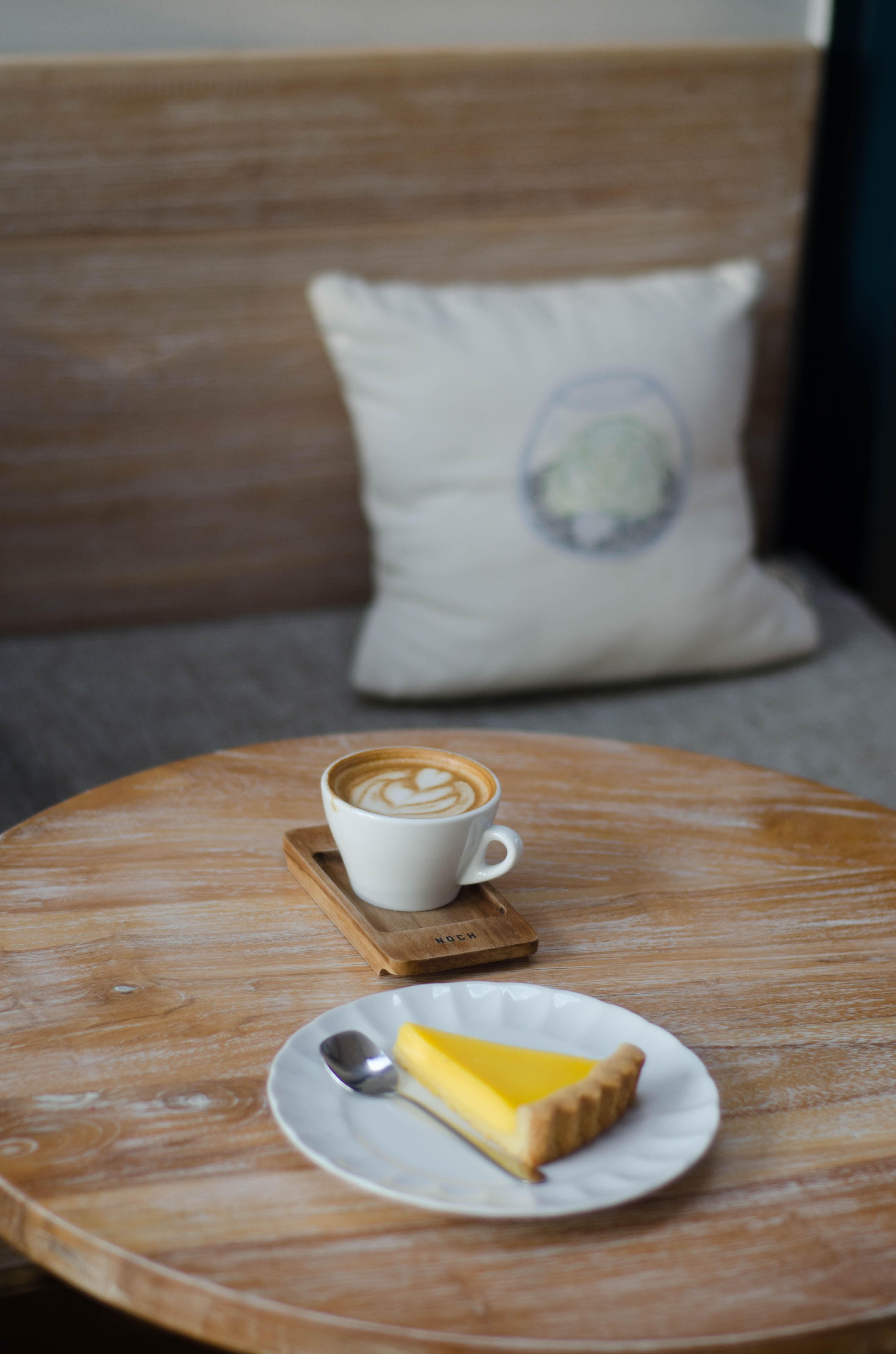 white ceramic teacup with cappuccino beside dessert on plate