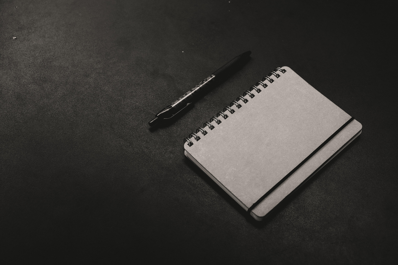 black click pen beside notebook