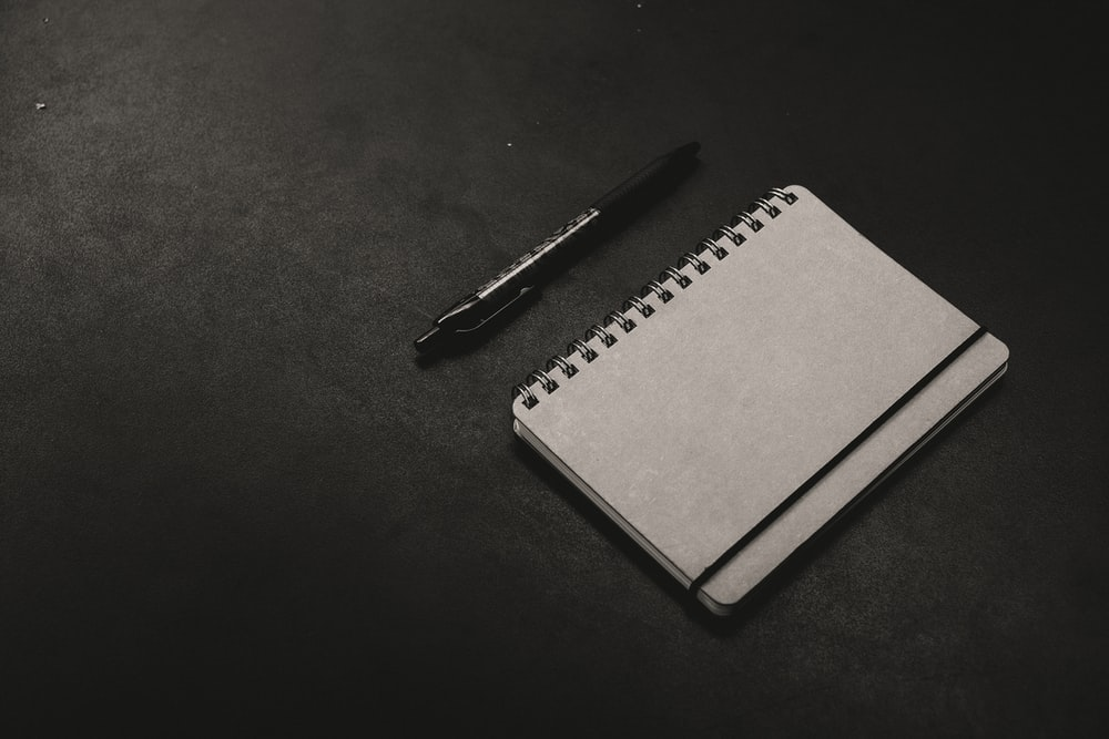 black click pen beside notebook