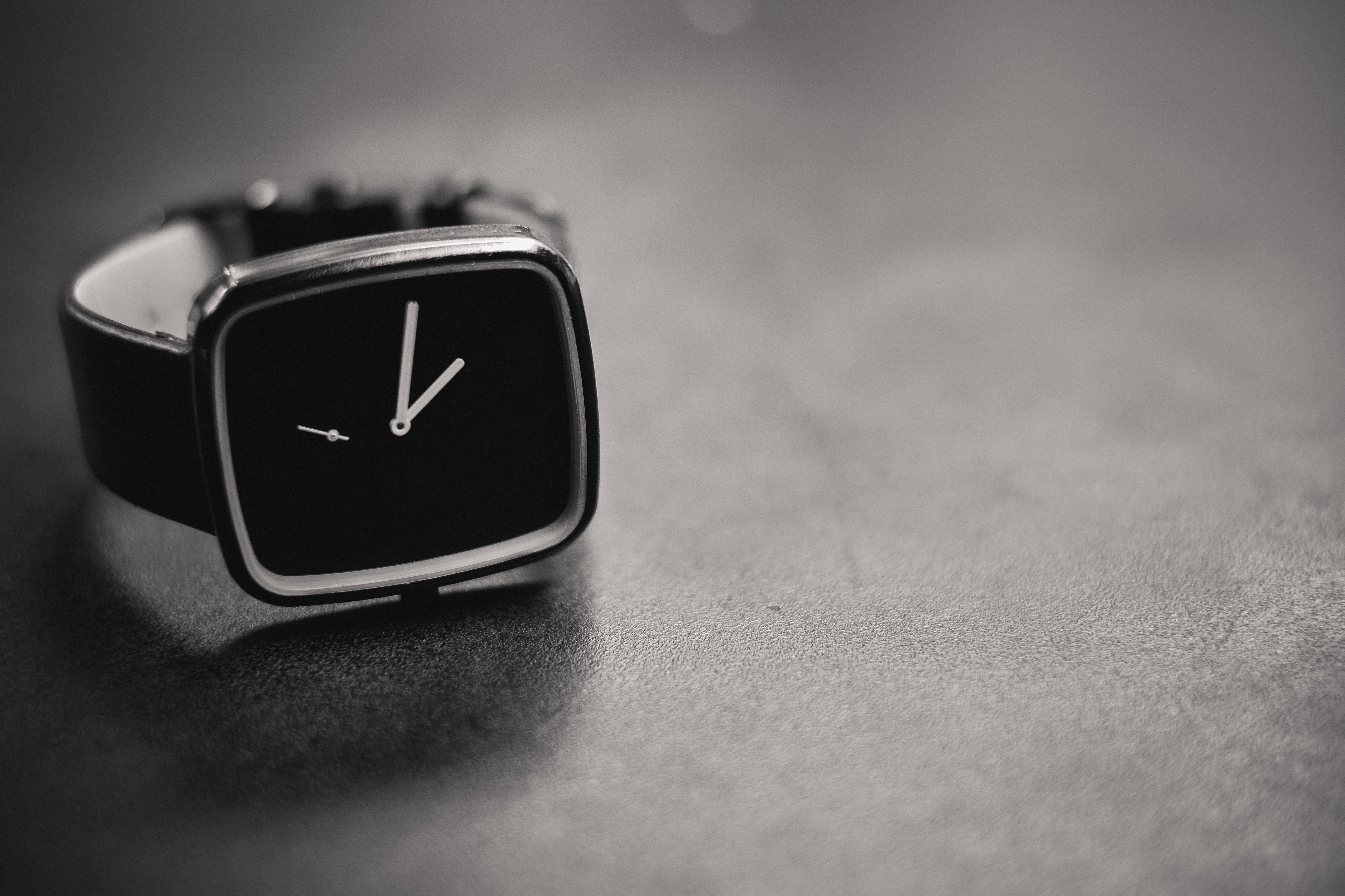 black and silver-colored analog watch showing 5:1