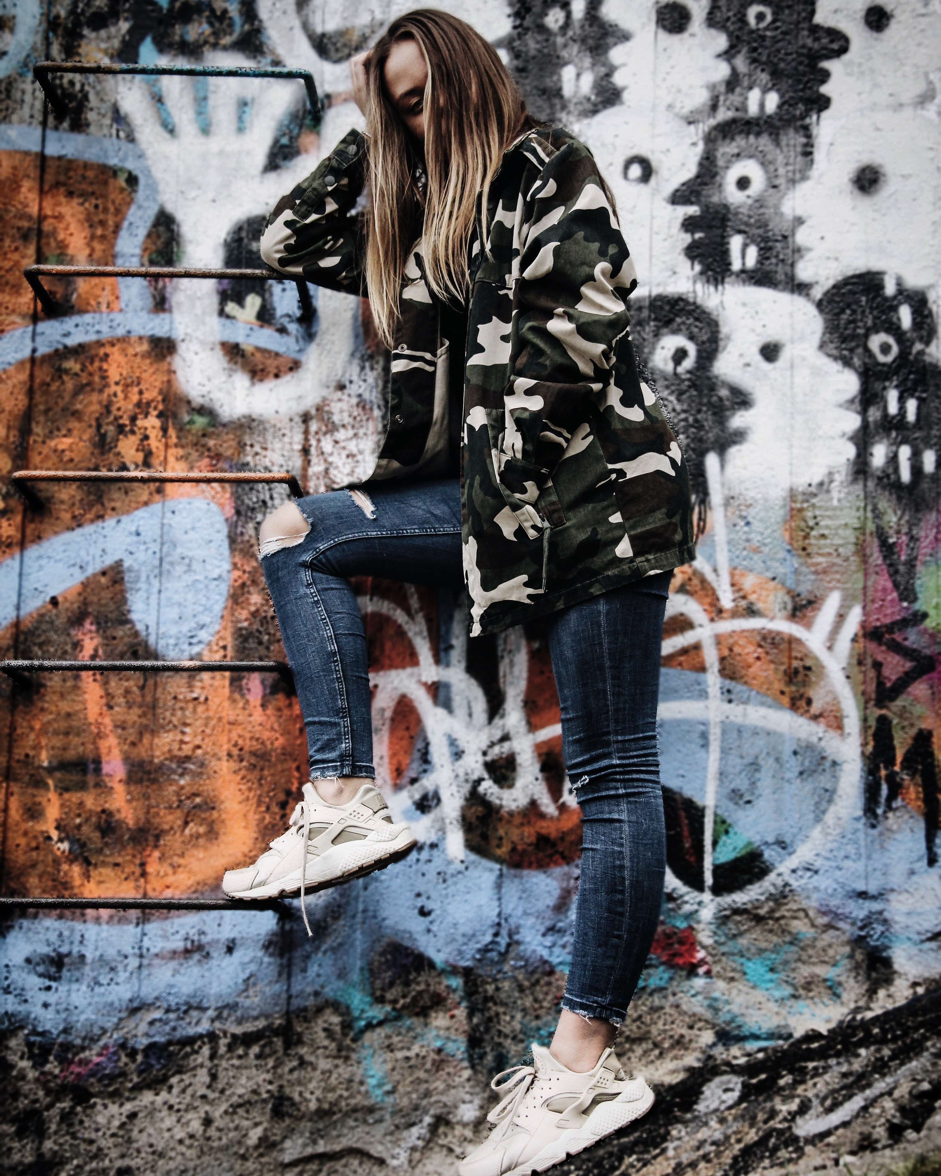 women's gray and black camouflage jacket standing beside wall