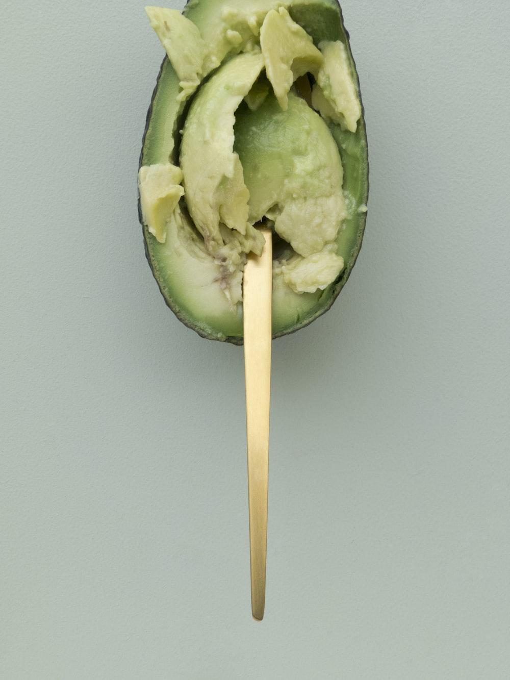 brown steel scoop on avocado