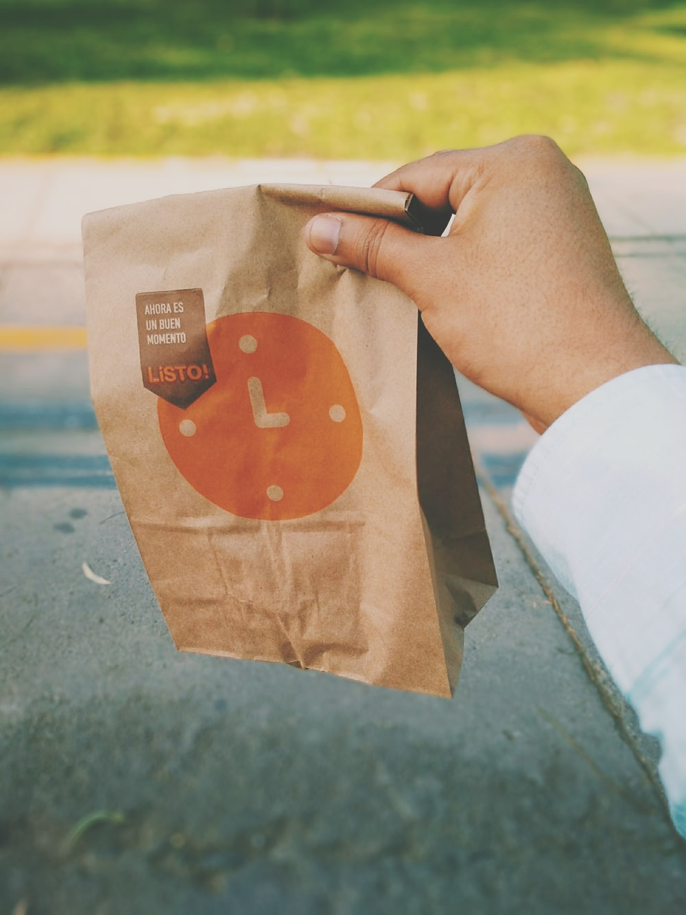 person holding brown Listo paper bag
