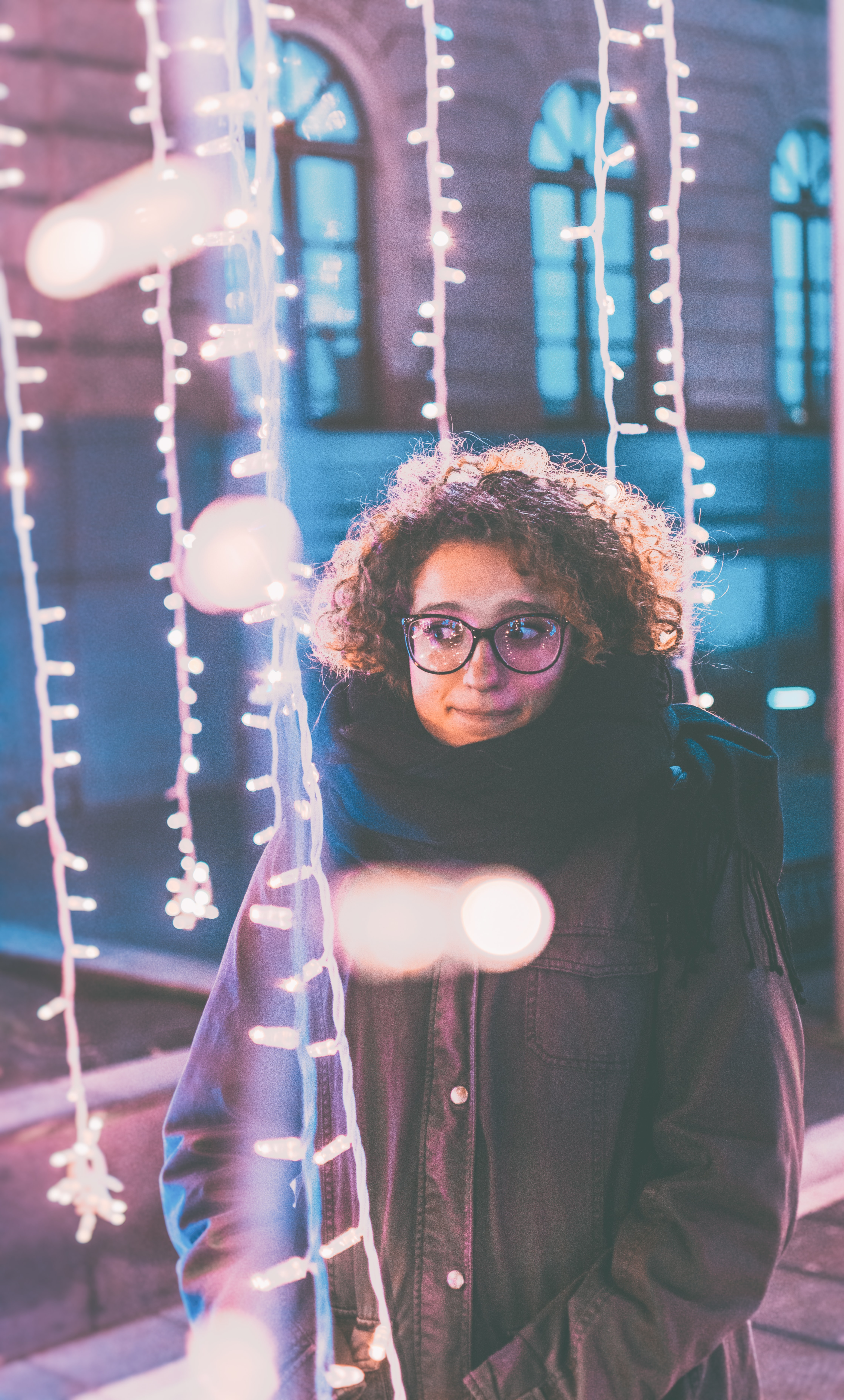 woman standing under lighted string lights