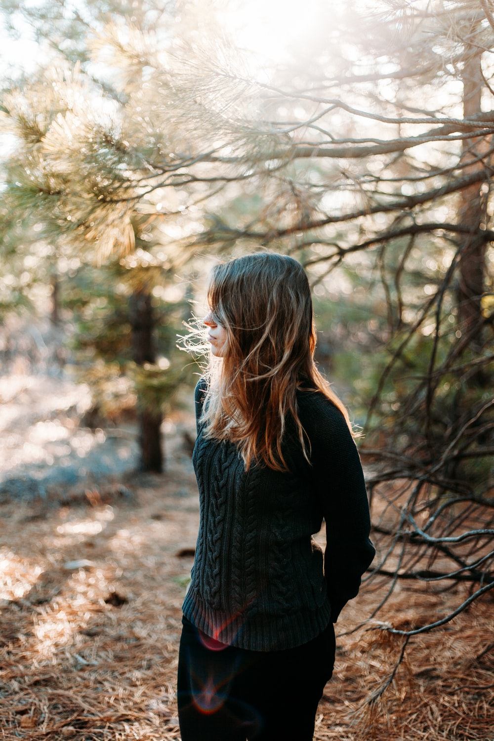 selective focus photography of woman standing beside tree