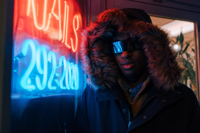 man in black full-zip hoodie leaning on neon light signage