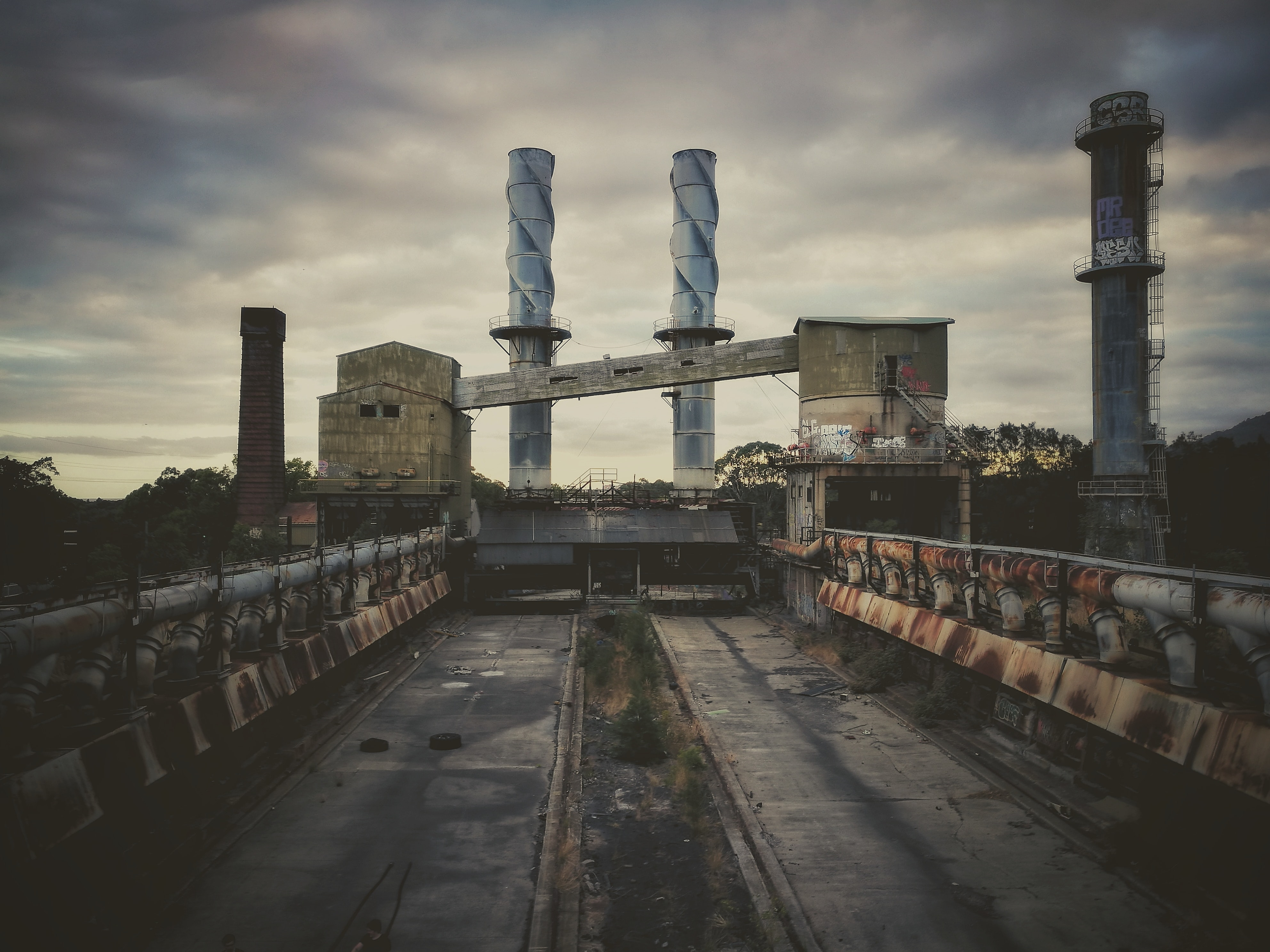 three metal smoke pipes on gray concrete field