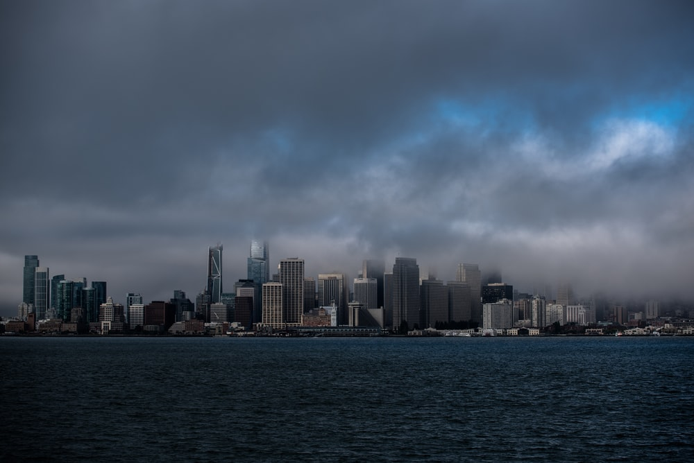 city with high-rise buildings viewing sea under gray skies