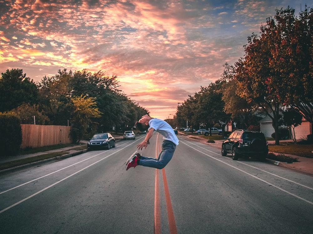 man jumping on road during golden hour