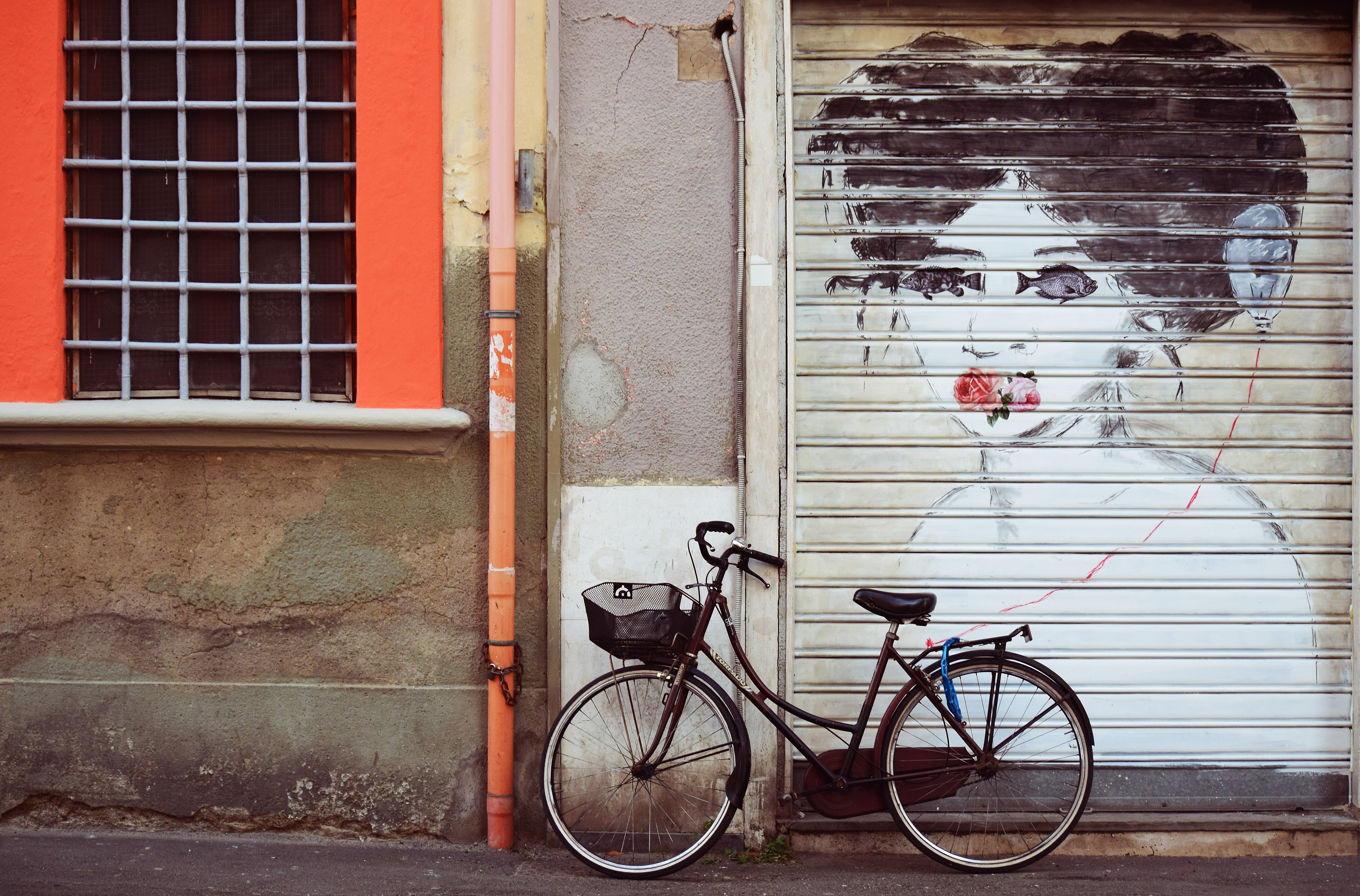black female bicycle leaning on gray wall