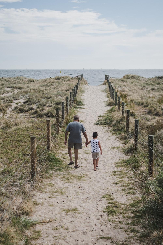 man and boy walking across pathway heading beach