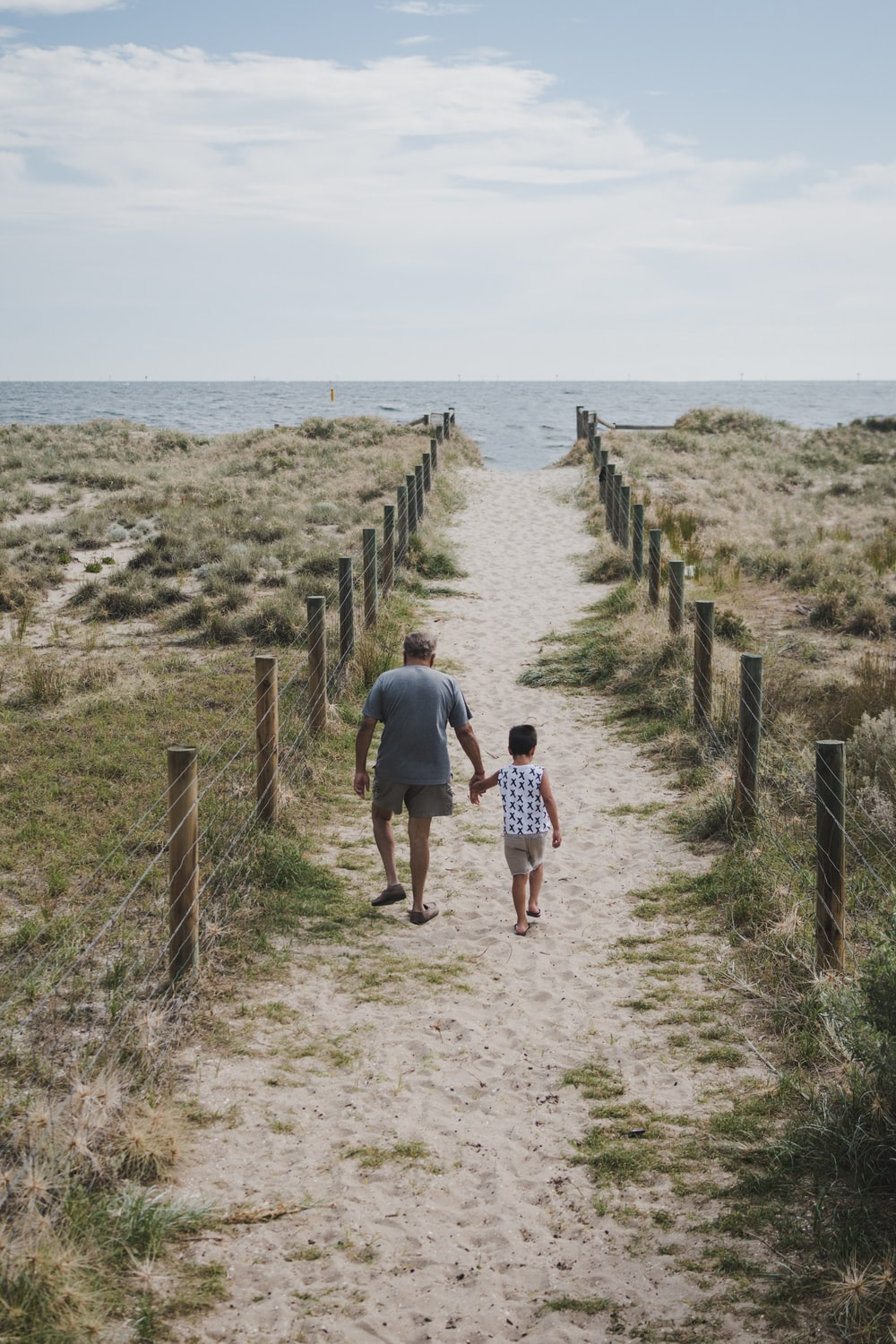 man and boy walking across pathway heading beach