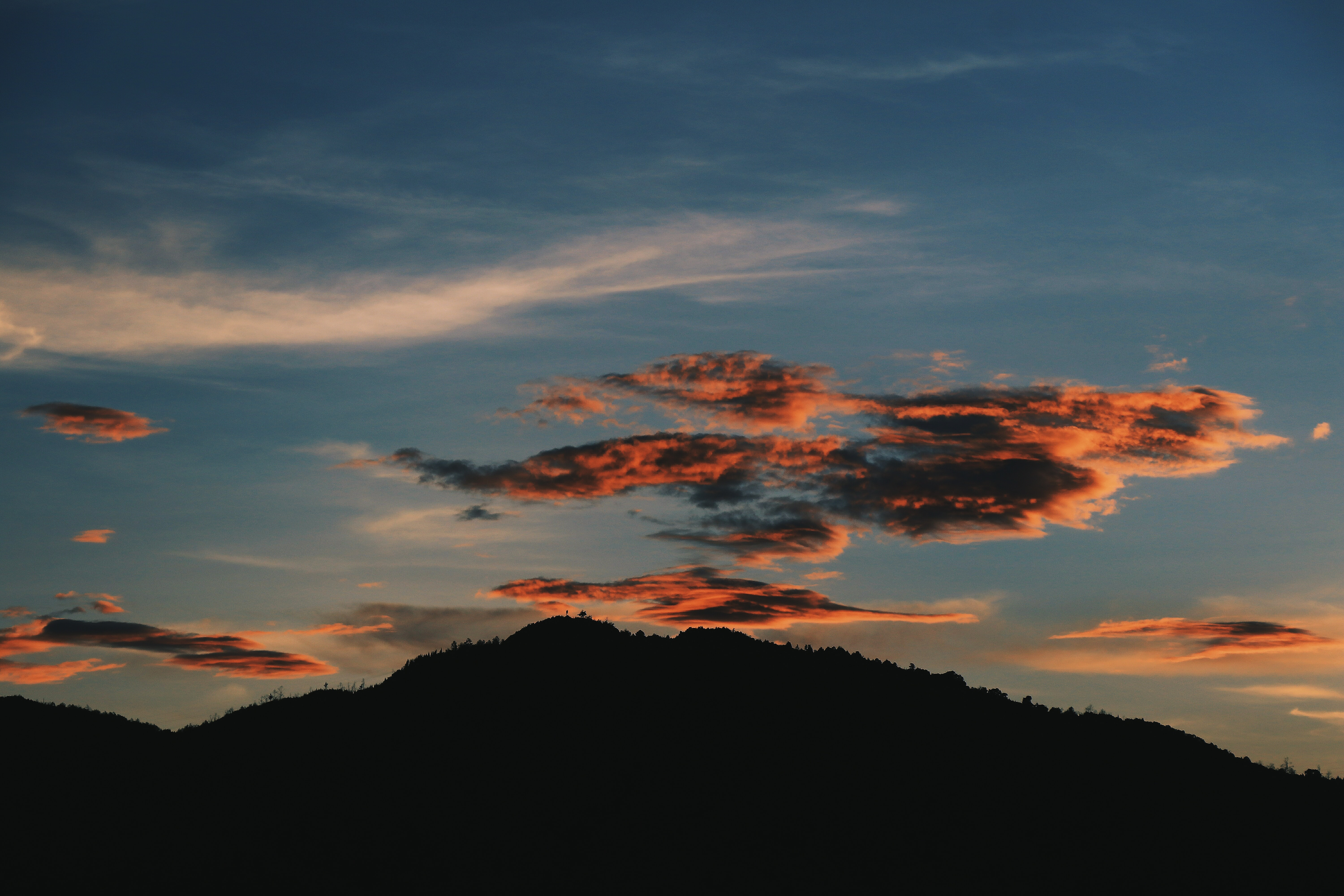 silhouette photography of mountain under nimbus clouds