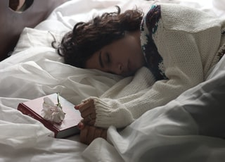 woman sleeping on bed beside book
