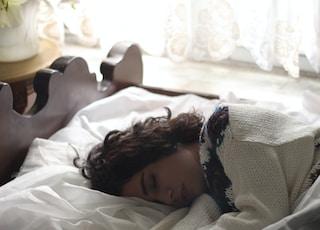 woman sleeping on bed beside book