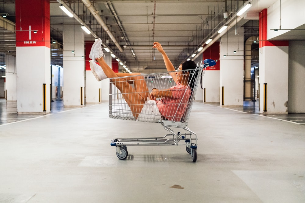 woman sitting in shopping cart at parking lot