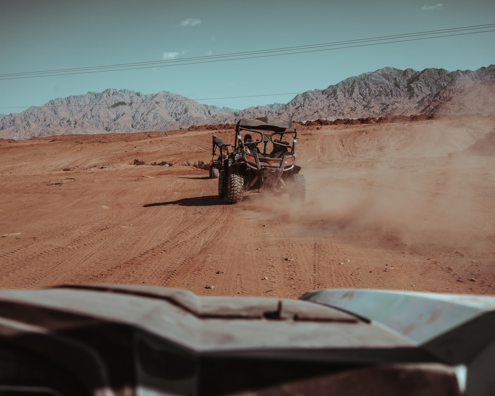 black and red ATV travelling on desert