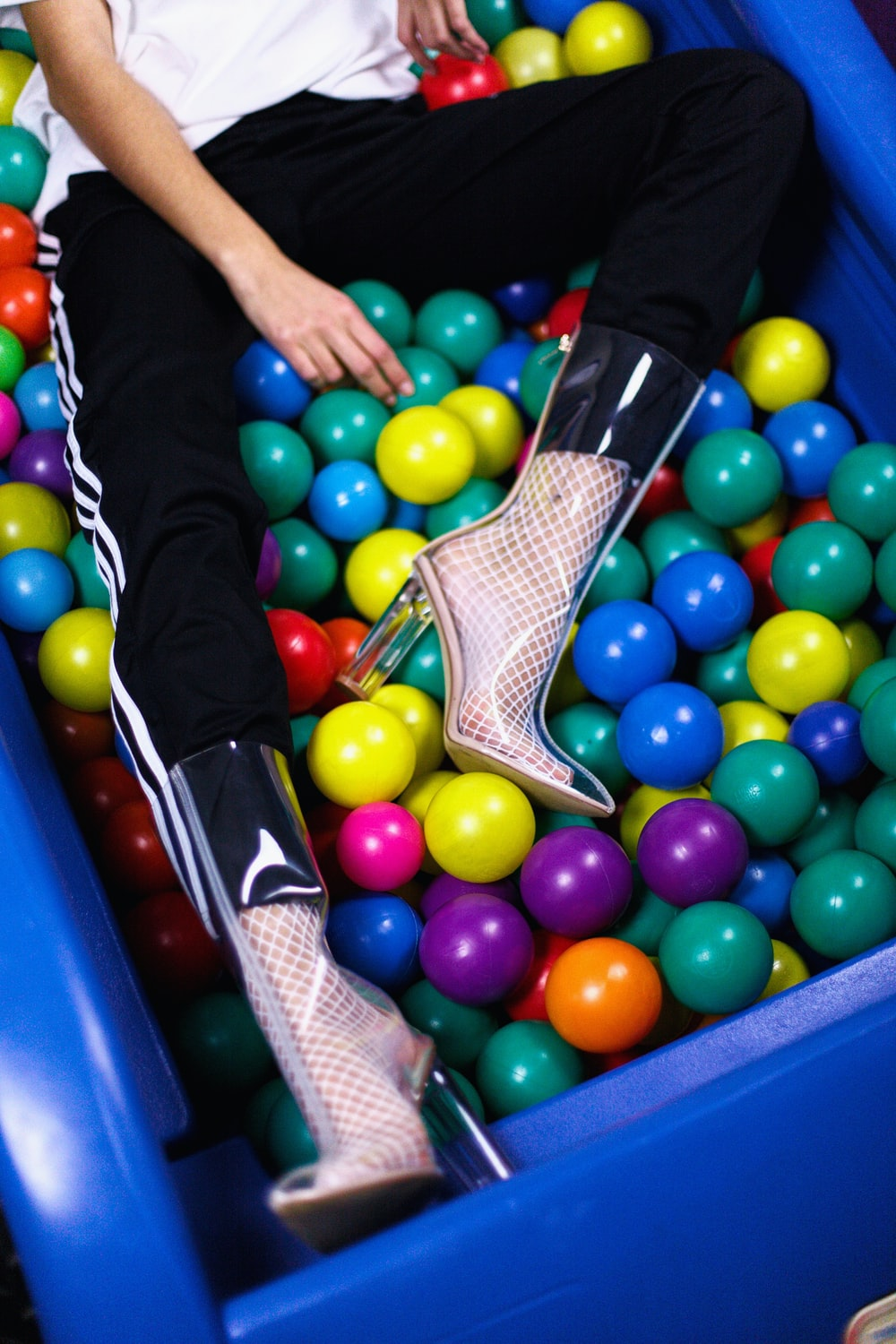 person sitting on assorted-color plastic ball lot