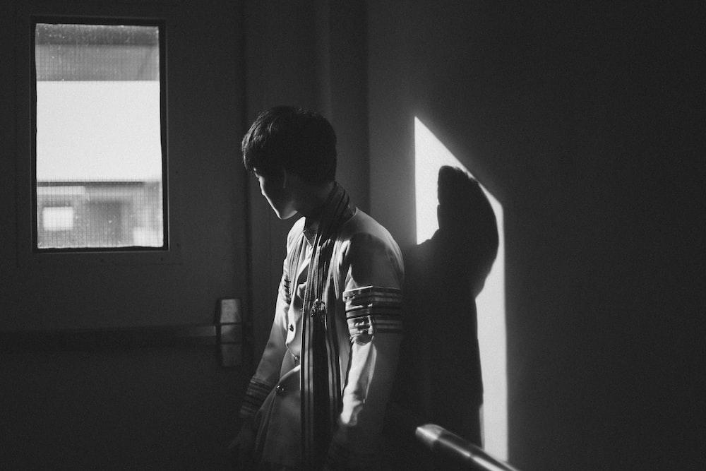 grayscale photography of man standing beside door