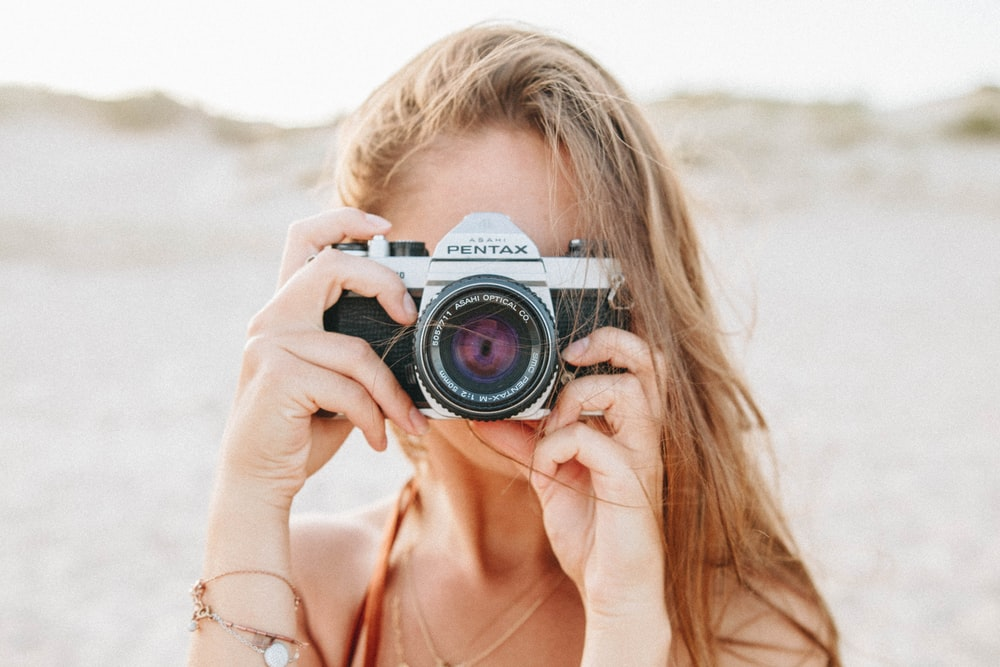 woman taking picture using silver Pentax camera