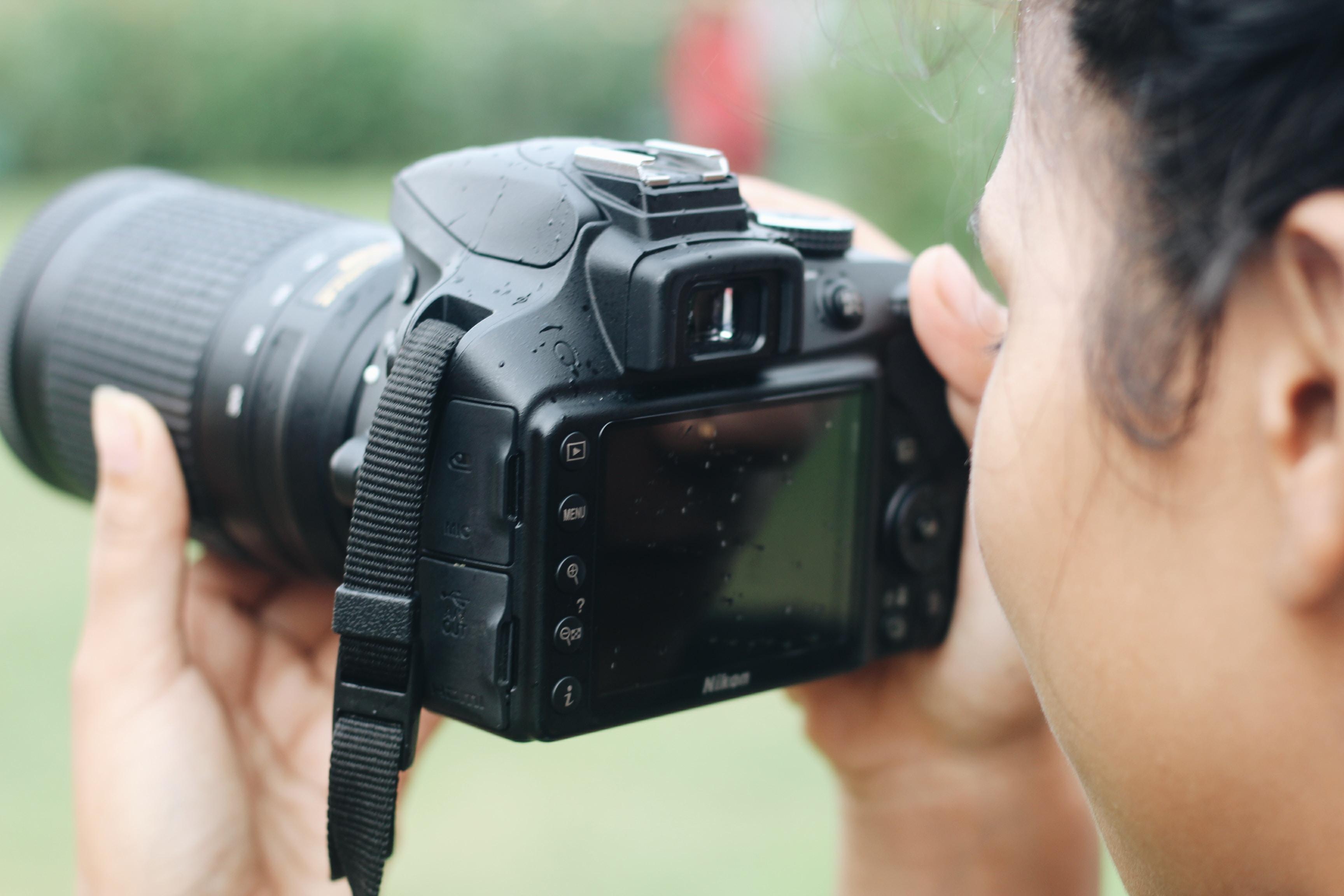 woman taking photos using Nikon DSLR camera during daytime