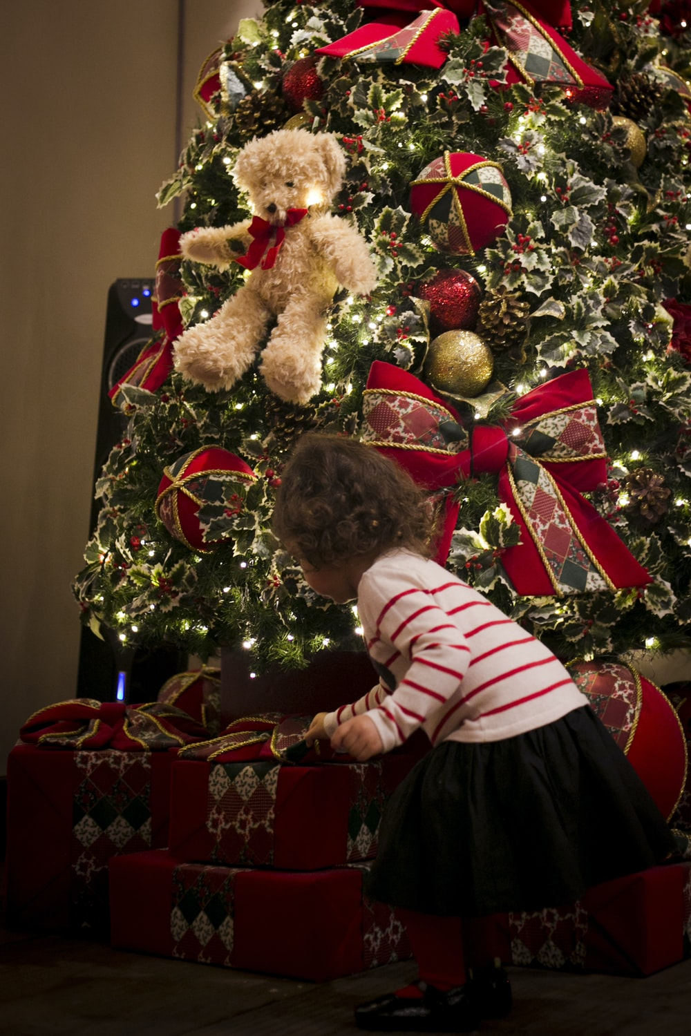 girl picking gift in front of pre-lit tree