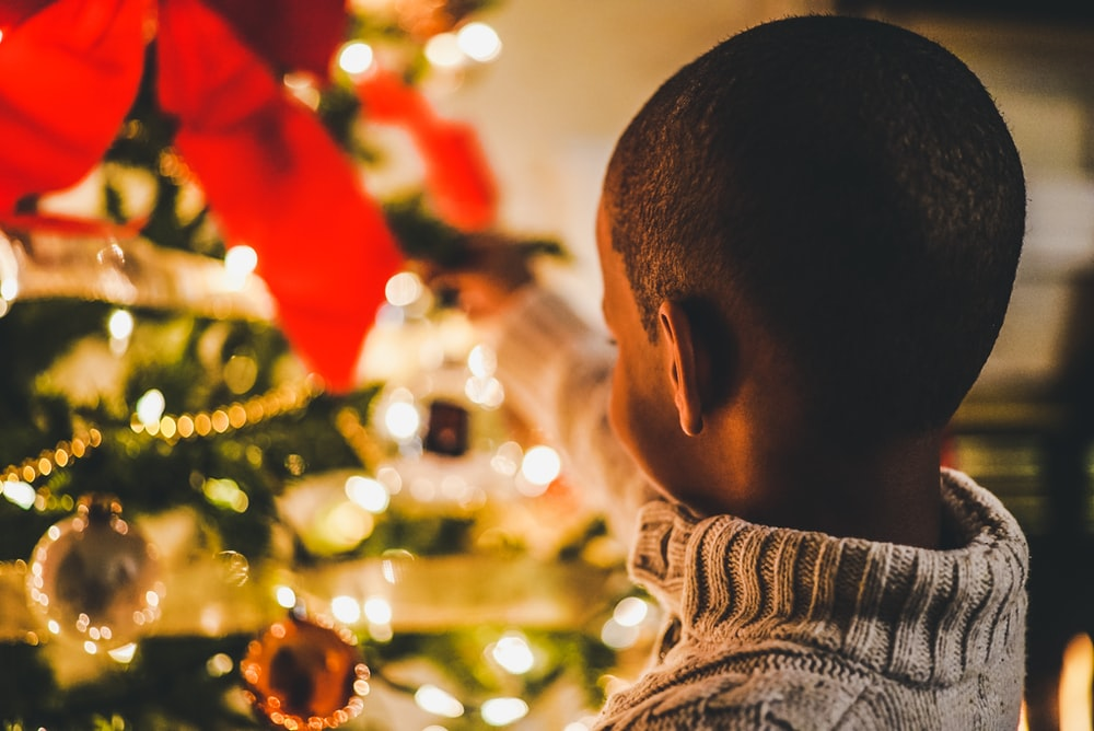 selective focus photography of boy near lit Christmas tree