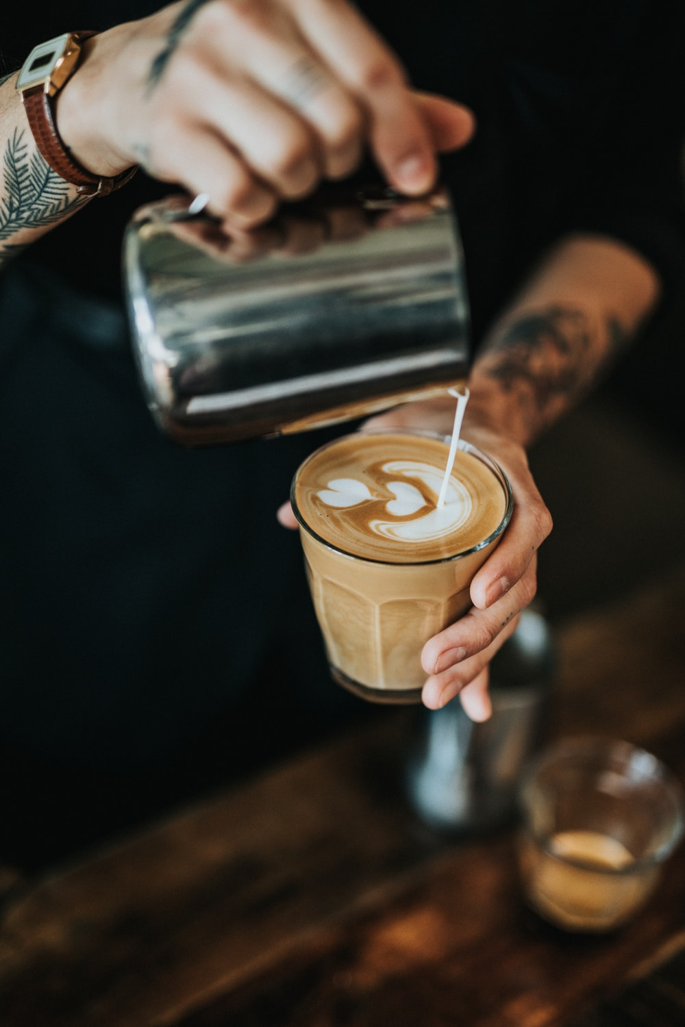 man pouring milk in coffee